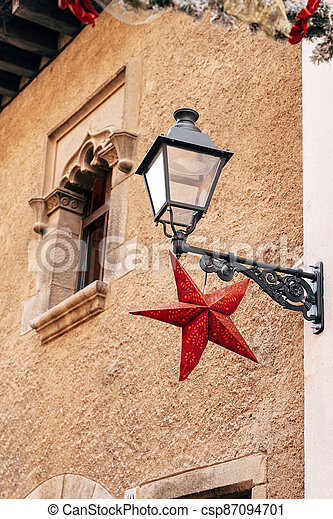A street lamp on a bracket on the wall of a house with a red star at the window with patterns in stone. - csp87094701