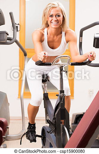 A stunning young woman using an exercise bike in the gym - csp15900080