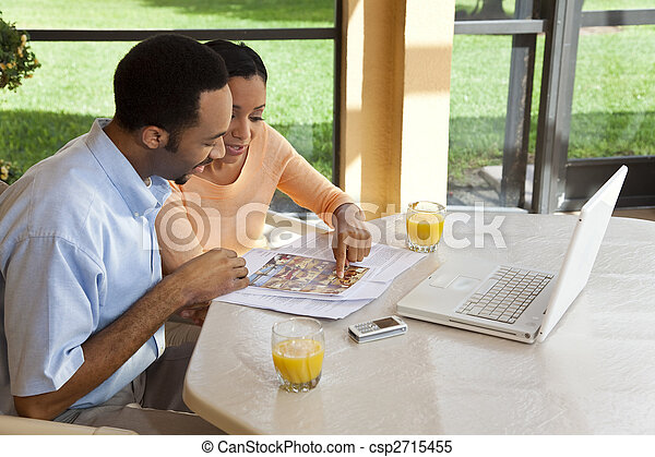 A successful African American man and woman couple in their thirties using a laptop computer to look for property on the internet - csp2715455