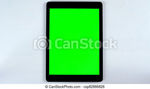 A tablet with a green screen lies on the table. Chroma Key on Gadget Screen. - csp82886826