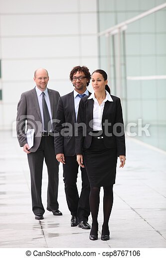 A team of businesspeople waking their way into their office block - csp8767106