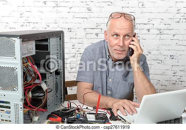 a technician repairing a computer and phone to the customer - csp27611919