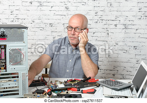 a technician repairing a computer and phone to the customer - csp27611537