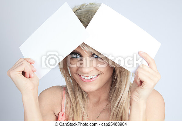 A Teenager girl hold white blank paper. Young smiling woman show - csp25483904