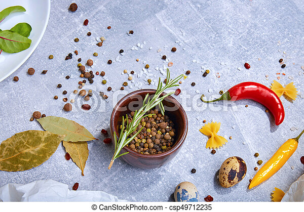 A top view of a brown wooden bowl with seasoning on a gray background. Spices with hot peppers, bay leaves and a rosemary twig. - csp49712235