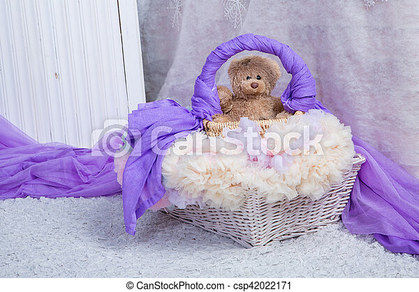 a toy bear sits in a basket in a bright room - csp42022171