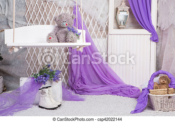 a toy bear sits in a basket in a bright room - csp42022144