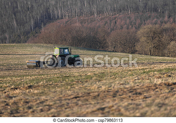 a tractor on a meadow in the evening - csp79863113