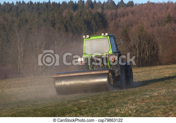 a tractor on a meadow in the evening - csp79863122