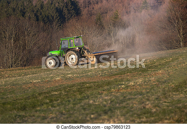 a tractor on a meadow in the evening - csp79863123