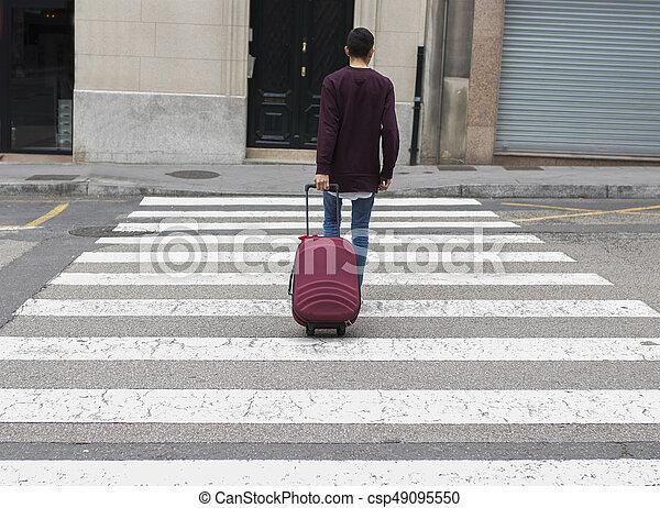 El joven de enfrente con la maleta - csp49095550