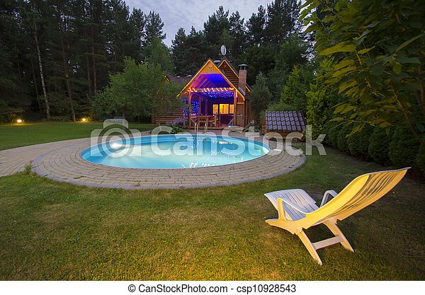 A waterpool with chair near wooden house at night - csp10928543