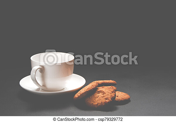 A white cup of coffee with homemade orange biscuits stands on black - csp79329772