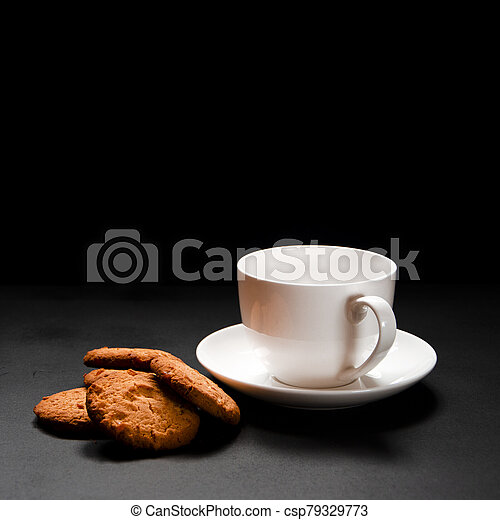 A white cup of coffee with homemade orange biscuits stands on black - csp79329773