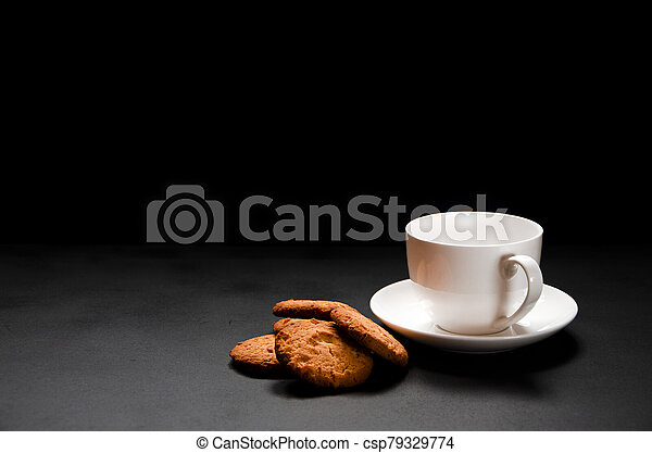 A white cup of coffee with homemade orange biscuits stands on black - csp79329774