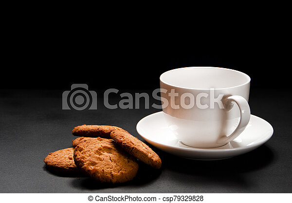 A white cup of coffee with homemade orange biscuits stands on black - csp79329828