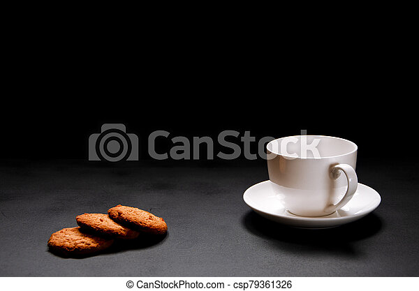 A white cup of coffee with homemade orange biscuits stands on black - csp79361326