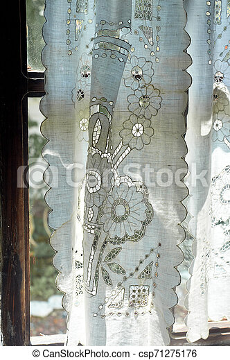 A window in a whitewashed hut with a wooden frame, a Lacy linen starched curtain. The interior of the house. Ukraine, the Cossacks - csp71275176