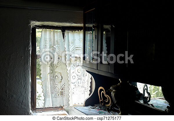 A window in a whitewashed hut with a wooden frame, a Lacy linen starched curtain. The interior of the house. Ukraine, the Cossacks - csp71275177
