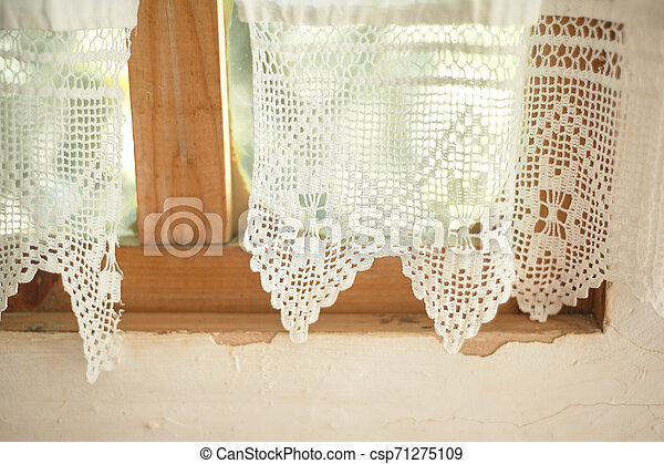 A window in a whitewashed hut with a wooden frame, a Lacy linen starched curtain. The interior of the house. Ukraine, the Cossacks - csp71275109