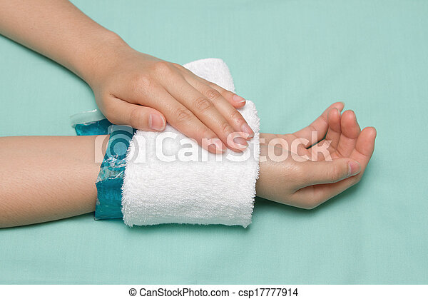 a woman applying cold pack on swollen hurting wrist after accident - csp17777914