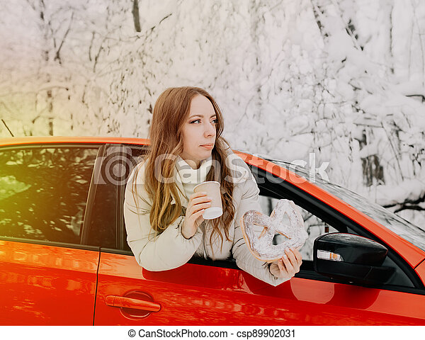 A woman drinks hot coffee and holds a bun in a red car in a winter forest. Sunshine. - csp89902031