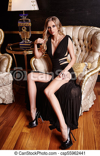 A woman in a black dress sitting on a chair. - csp55962441