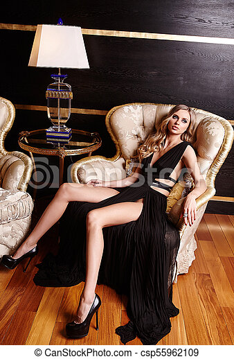 A woman in a black dress sitting on a chair. - csp55962109