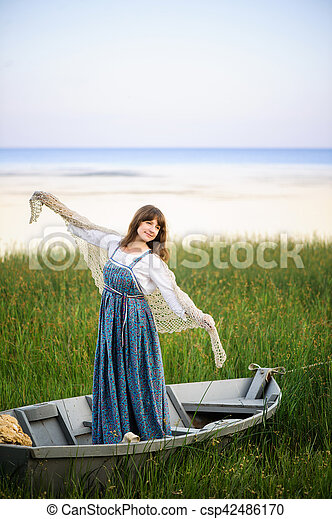 a woman in a boat on the shore - csp42486170