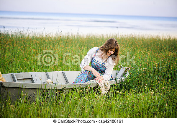 a woman in a boat on the shore - csp42486161