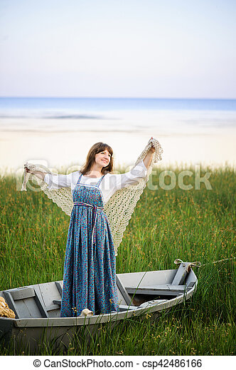 a woman in a boat on the shore - csp42486166