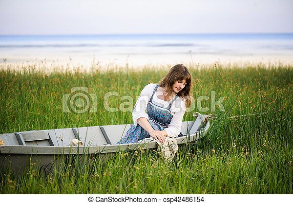 a woman in a boat on the shore - csp42486154