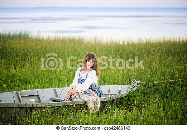 a woman in a boat on the shore - csp42486143