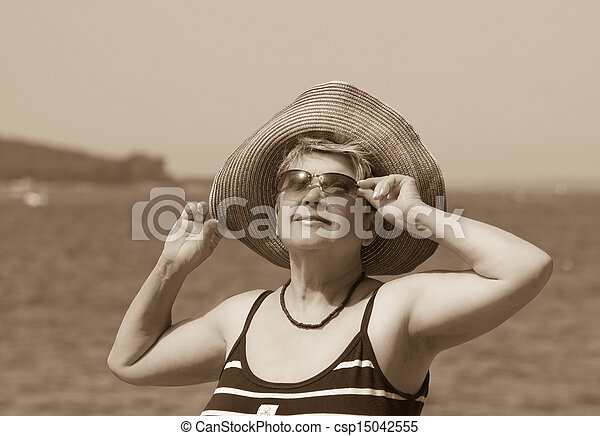 A woman in a hat on a background of the sea - csp15042555