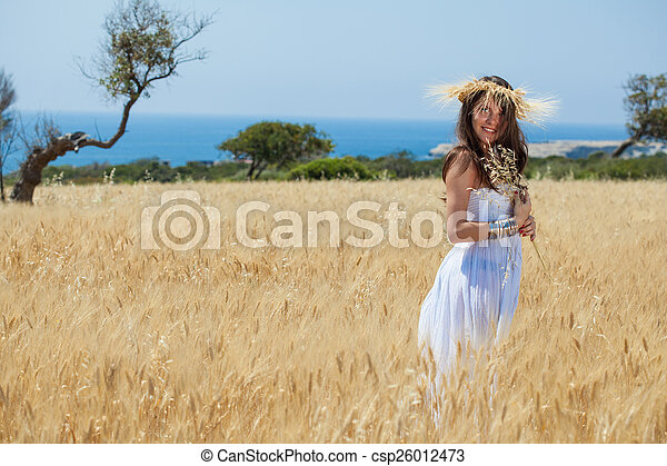 A woman is in the field with a wreath - csp26012473