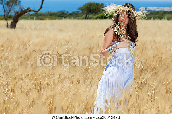 A woman is in the field with a wreath - csp26012476