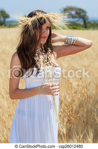 A woman is in the field with a wreath - csp26012480