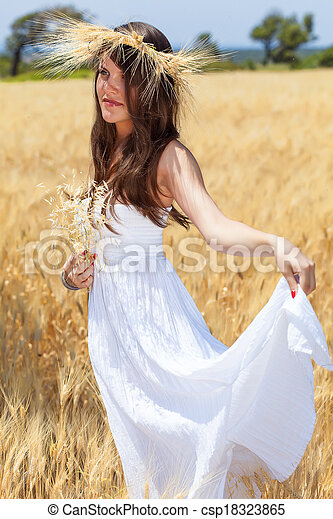 A woman is in the field with a wreath - csp18323865