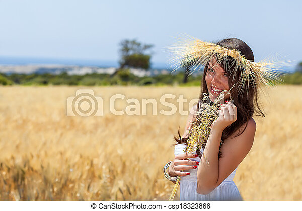 A woman is in the field with a wreath - csp18323866