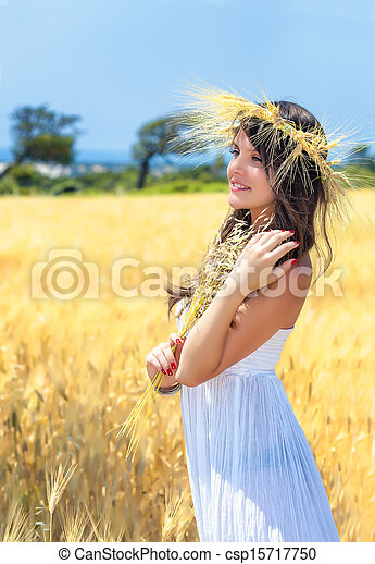 A woman is in the field with a wreath - csp15717750