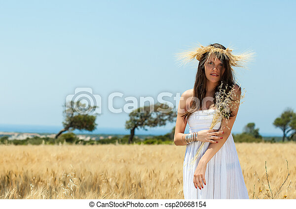 A woman is in the field with a wreath - csp20668154