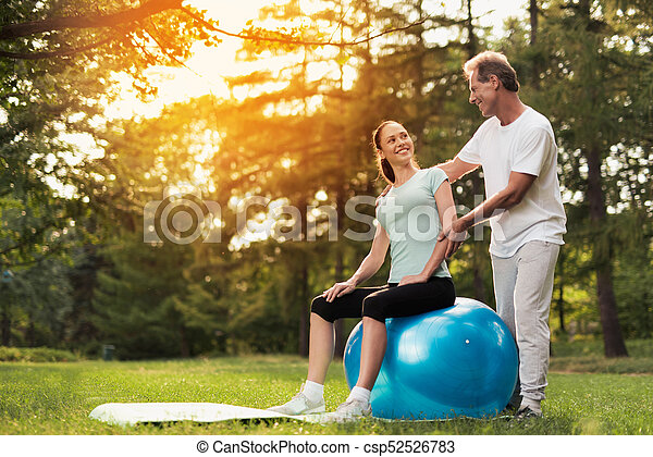 A woman is sitting on a ball for yoga. A man is standing behind and looking at her. - csp52526783