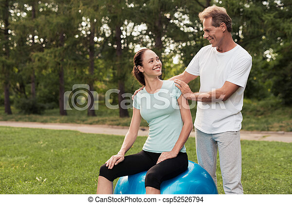 A woman is sitting on a ball for yoga. A man is standing behind and looking at her. - csp52526794