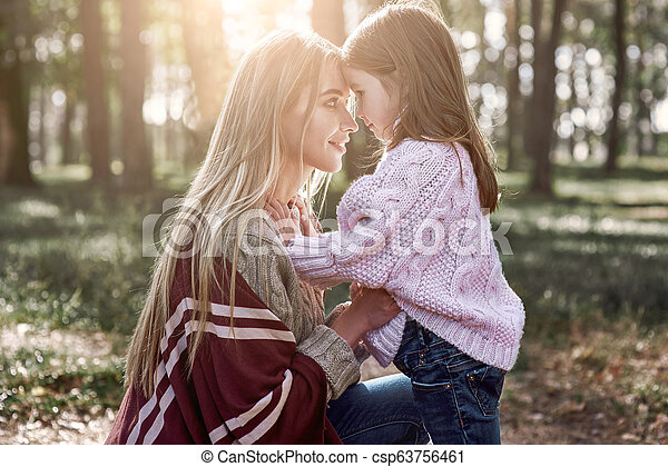 A woman kisses her mother in forest - csp63756461