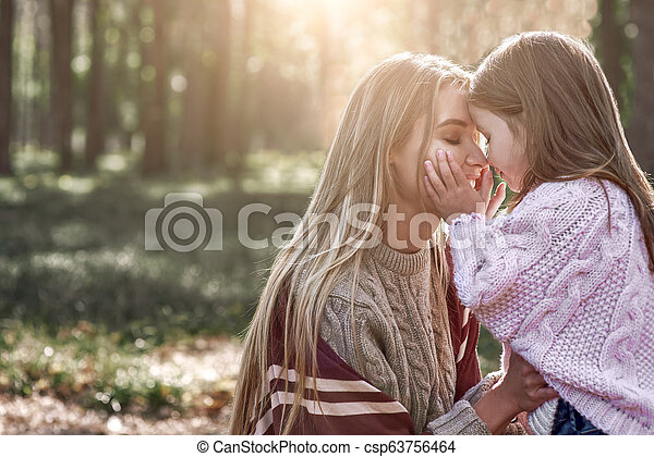 A woman kisses her mother in forest - csp63756464