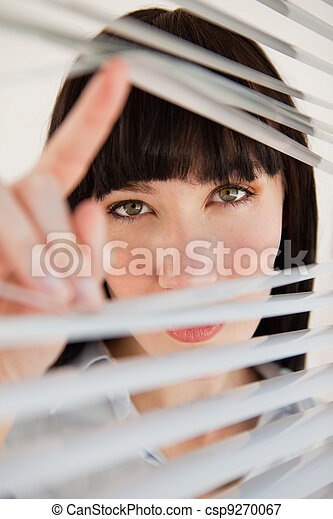 A Woman Looking Through Some Blinds Into The Camera A