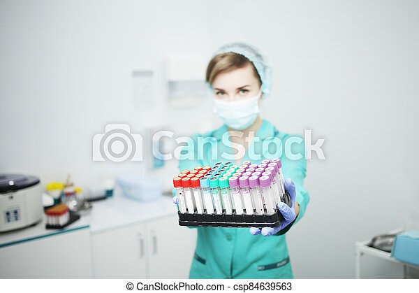 A woman nurse doctor in a medical mask holds test tubes for a blood test - csp84639563