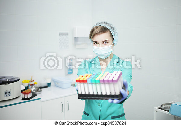 A woman nurse doctor in a medical mask holds test tubes for a blood test - csp84587824