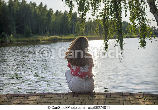 A woman sits on the shore of a lake at sunset - csp86274011