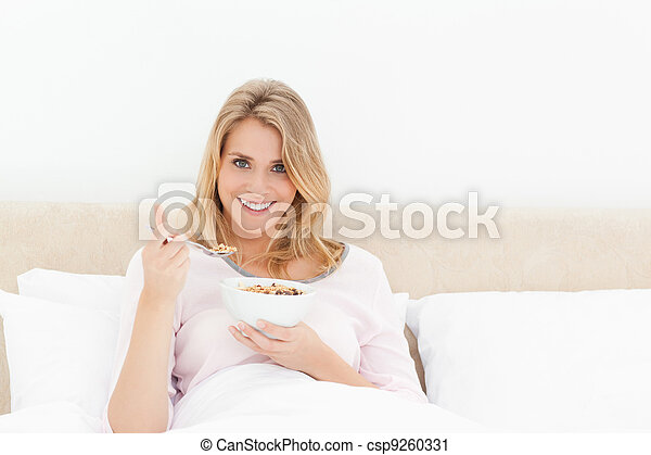 A woman sitting upright in bed with a bowl and spoon of cereal in her hands, smiling and looking ahead. - csp9260331